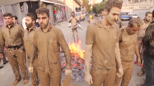 iranian shiite muslims cover themselves with mud during the 'kharrah mali' ritual to commemorate the day of ashura which marks the anniversary of the... - ashura muharram stock-videos und b-roll-filmmaterial