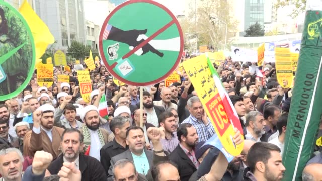 iranians take part in an antius rally in front of the former us embassy in tehran on november 04 to mark the 40th anniversary of the us embassy... - イラン点の映像素材/bロール