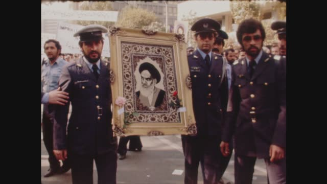 iran/iraq war; 22.9.1980 iran: tehran: ext iranian airmen cheer and wave at mass demonstration airmen carry picture of ayatollah khomeini itn file:... - イラク点の映像素材/bロール