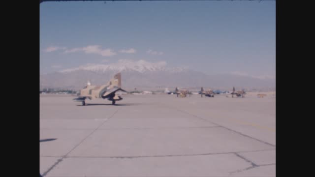 iran/iraq war; itn file: 27.4.78 iran: bv iranian air force fighter jet taxis on runway int air traffic control personnel in airport control tower... - イラク点の映像素材/bロール