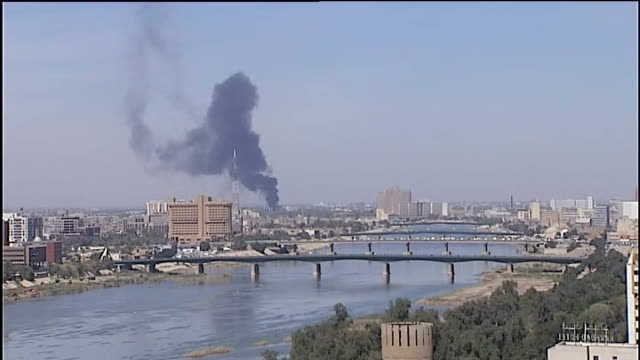 Sixty die in bomb blasts Long shot of large plume of smoke rising over Baghdad skyline High angle shot of busy traffic roundabout overlooked by large...