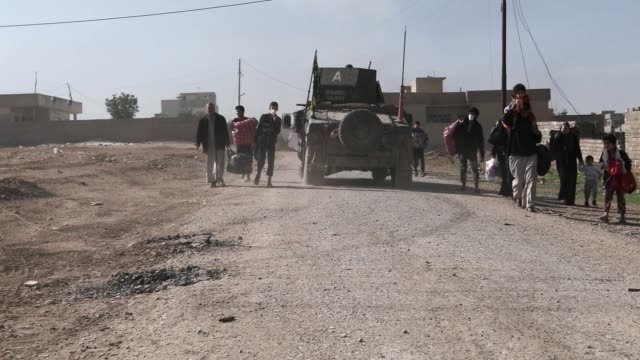 a iraqi armored vehicle drives by civilians fleeing the city of mosul thousands of civilians have fled the city of mosul due to the war against the... - isis stock videos and b-roll footage