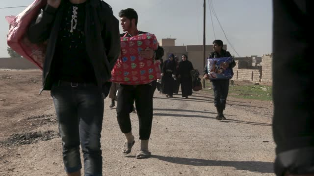 a iraqi armored vehicle drives by civilians fleeing the city of mosul thousands of civilians have fled the city of mosul due to the war against the... - civilperson bildbanksvideor och videomaterial från bakom kulisserna