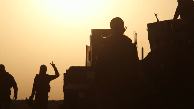 iraqi army soldiers taking a break at dawn on the outskirts of mosul after a brief pause in fighting with islamic state militants - in silhouette stock videos & royalty-free footage