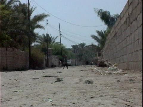 iraqi civilians walking down alley / mahmudiyah, iraq / audio - 男児のみ点の映像素材/bロール