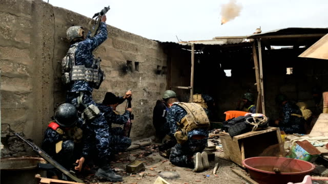 Iraqi federal police officers attack an Islamic State position on a nearby rooftop in west Mosul Iraqi forces backed by US and British air support...