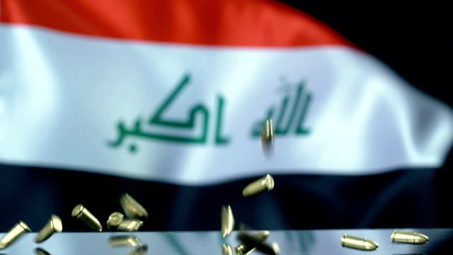 iraqi flag behind bullets falling in slow motion - iraqi flag stock videos and b-roll footage