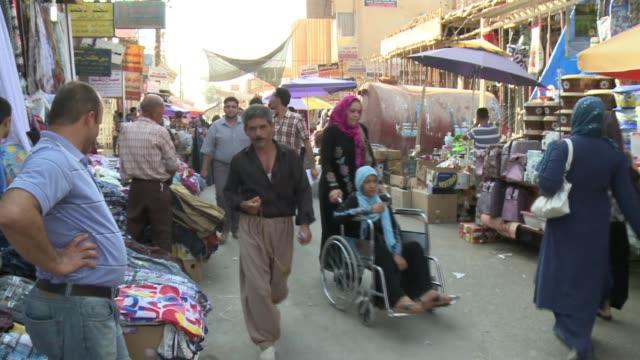 iraqi kurds shop in kirkuk market includes woman in wheel chair and people in traditional clothing. - 僧衣点の映像素材/bロール