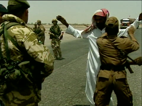 iraqi man being searched by british troops and iraqi civil defence corps at road block basra 25 may 04 - bassora video stock e b–roll