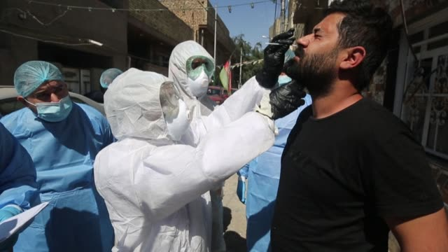 iraqi medical staffers test the residents of sadr city, on the outskirts of baghdad, for novel coronavirus and distribute awareness pamphlets as part... - iraq video stock e b–roll