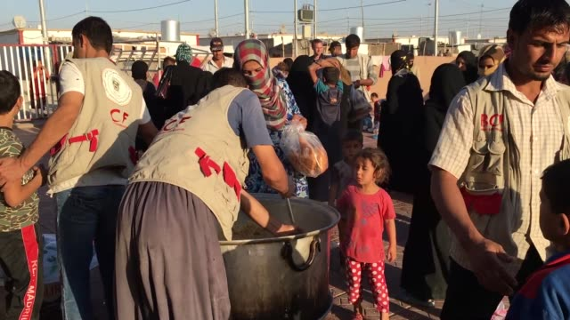 iraqi men are given food in debaga refugee camp where newly arrived refugees from mosul have sought shelter as the ongoing offensive to retake mosul... - human joint stock videos & royalty-free footage