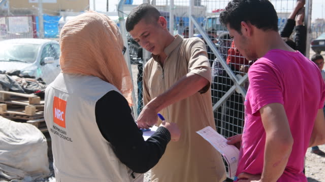iraqi men queue for food and hygiene kits at debaga refugee camp where newly arrived refugees from mosul have sought shelter as the ongoing offensive... - human joint stock videos & royalty-free footage