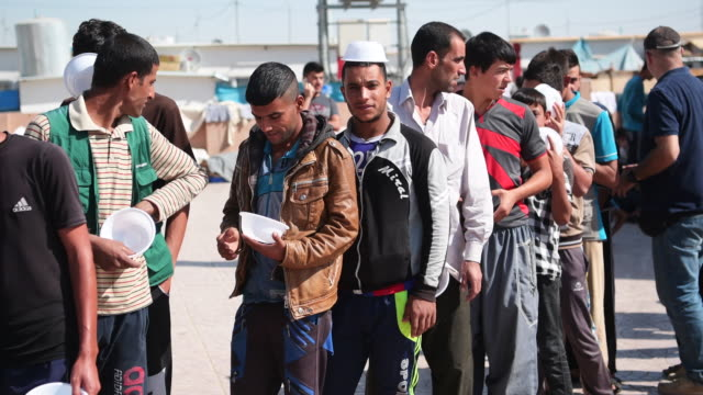 iraqi men queue for food in debaga refugee camp where newly arrived refugees from mosul have sought shelter as the ongoing offensive to retake mosul... - human joint stock videos & royalty-free footage