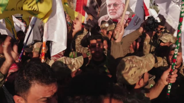 iraqi militia, the popular mobilisation forces, chanting and waving flags in front of poster to killed iranian general qasem soleimani and iraqi... - イラク点の映像素材/bロール