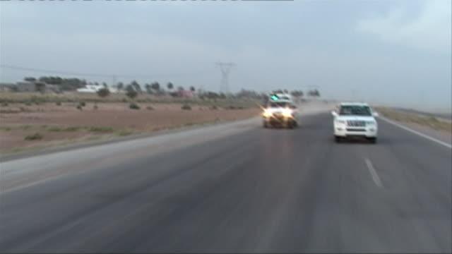 ws rear pov iraqi patrol vehicle speeding down road, haditha, al anbar, iraq - 乗物後部から見た視点点の映像素材/bロール