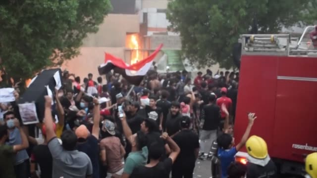 vídeos y material grabado en eventos de stock de iraqi protesters gather in mass during an anti government demonstration outside the burning local government headquarters in nasiriyah the capital of... - nasiriyah