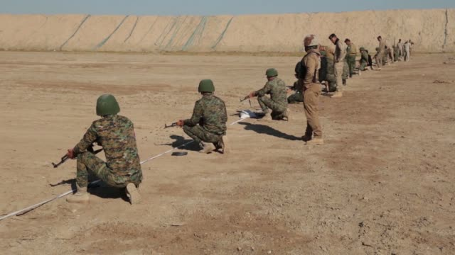 stockvideo's en b-roll-footage met iraqi security forces instructors conduct training with isf soldiers in firing the ak47 assault rifles at al taqaddum firing range iraq july 3 2019 - ontslaan
