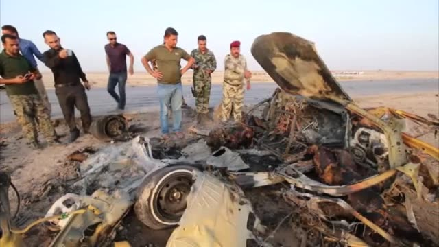Iraqi security officials inspect the site of a car bomb attack targeting a checkpoint in Iraq's southern Dhi Qar province province on September 14...
