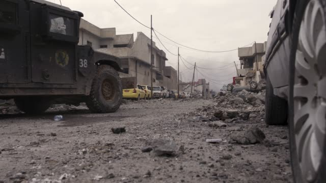 iraqi special operations forces armored vehicle driving through the destroyed streets of mosul. the military operation to liberate the city of mosul... - irak stock-videos und b-roll-filmmaterial