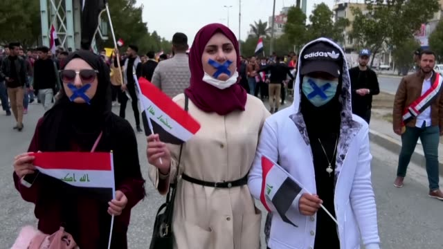 iraqi students march with blue cross marks on their faces in protest of the lack of freedom of speech as they participate in an anti government... - karbala stock videos & royalty-free footage