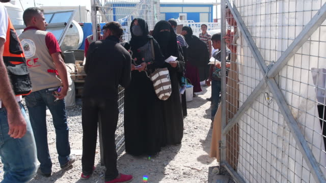 iraqi women and children queue for food and hygiene kits at debaga refugee camp where newly arrived refugees from mosul have sought shelter as the... - human joint stock videos & royalty-free footage