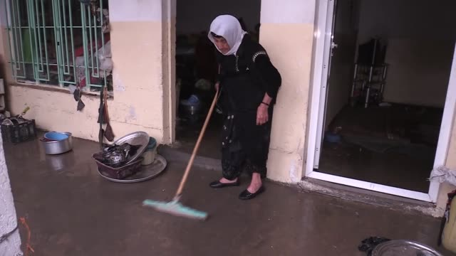 Iraqis clean their homes and shops as floodwater recedes in Erbil on February 18 2018 Iraqi Siyamend Rahman and Muhlis Sadik speak to reporters on...