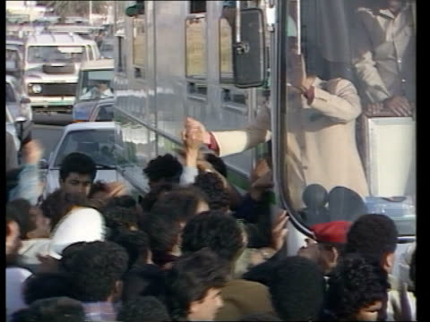 vídeos de stock, filmes e b-roll de arms find / libya col gaddafi libyan/ tunisian border ms gol muamar gaddafi standing at windsceen of bus waving reaches out of side window and shakes... - líbia
