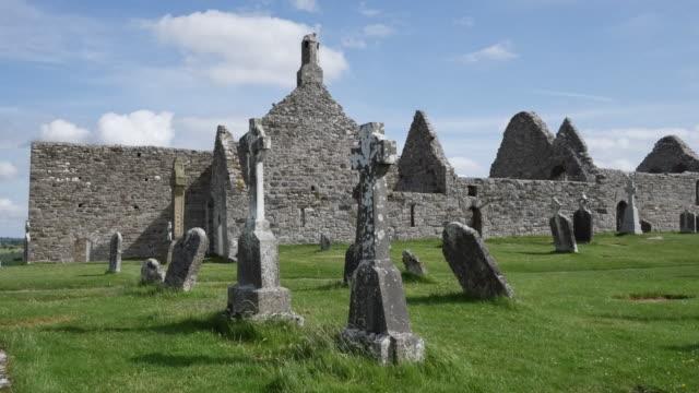 ireland clonmacnoise celtic crosses mark graves beside the cathedral ruins - 宗教上のシンボル点の映像素材/bロール