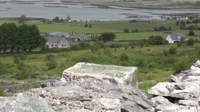 Ireland County Clare stone wall on hillside above estuary zoom and tilt up
