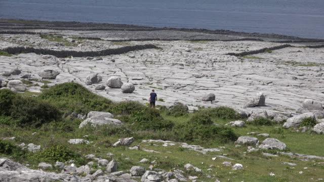 Ireland County Clare the Burren at Black Head with man walking toward walls