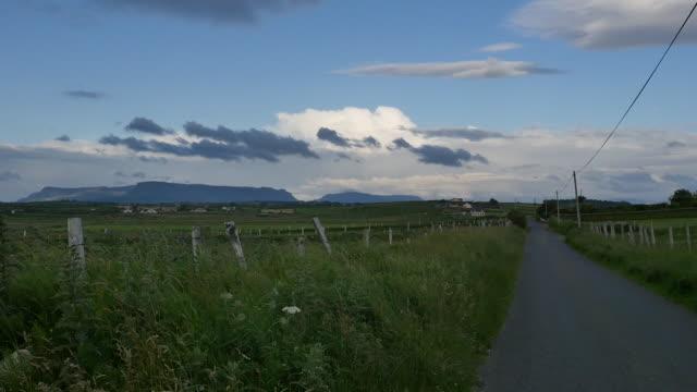 ireland county sligo a country road with distant benbulbin - mythologie stock-videos und b-roll-filmmaterial
