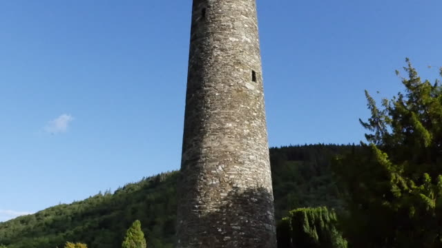 ireland glendalough round tower at celtic monastery ruin tilt up - schist stock videos and b-roll footage