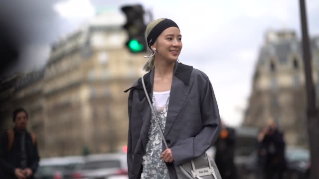 Irene Kim wears a bandanna a gray coat a lace dress a gray bag leggings outside Miu Miu during Paris Fashion Week Womenswear Fall/Winter 2018/2019 on...