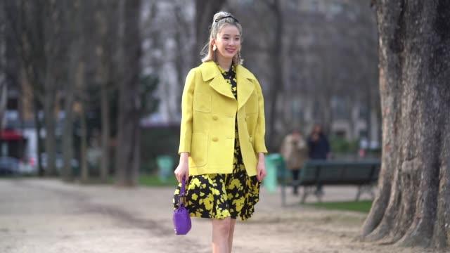 Irene Kim wears a yellow jacket a flower print dress a purple bag yellow shoes during Paris Fashion Week Womenswear Fall/Winter 2018/2019 on February...