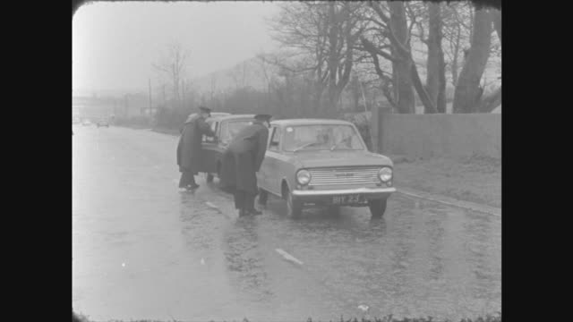 newry border post: c) policeman to armoured car: another to car in b/g bv as policeman goes to car: zoom in neg 16mm barron 10 secs 6 ft 17/4/66/6.3pm - b rolle stock-videos und b-roll-filmmaterial