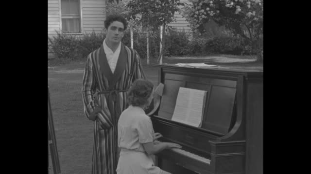 """irish boxer/singer jack doyle, wearing a striped robe, sings irish song """"come back to erin"""" accompanied by wife judith allen on outdoor spinet piano... - pesi massimi video stock e b–roll"""