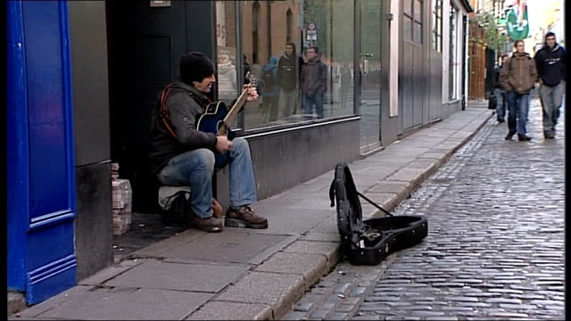 general views of dublin; man busking in street playing guitar as people walk past / close up busker playing guitar / low angle gvs from cobbled... - plucking an instrument stock videos & royalty-free footage