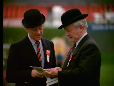 2 Irish men in suits + derbies looking at paper / look up