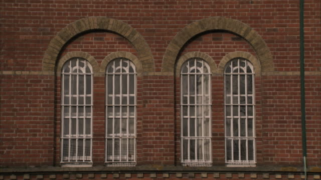 iron bars cover the arched windows of the broadmoor hospital in berkshire england. available in hd. - iron bars for windows stock videos & royalty-free footage