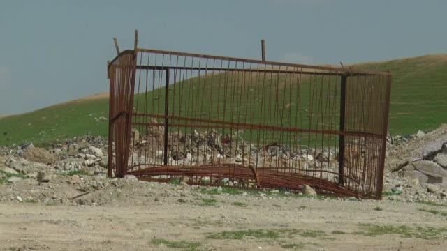 iron cages which belong to daesh militants and are used for torture to their prisoners seen at a garbage site in southern of mosul on march 28 2017 - folter stock-videos und b-roll-filmmaterial