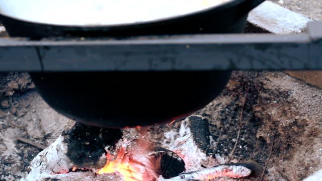 Iron cast cauldron boiling a stew over open log fire
