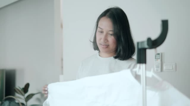 vidéos et rushes de fer son tissu-femme faisant le travail de maison dans le salon - vidéo de stock - vêtement de peau