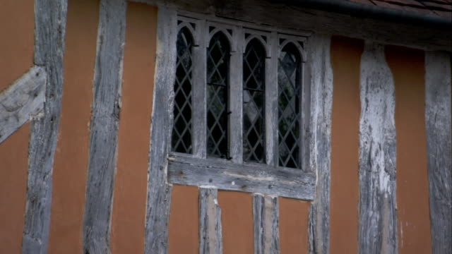 iron latticework fills the windows of a half-timbered home. available in hd. - lavenham stock-videos und b-roll-filmmaterial