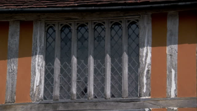iron latticework fills the windows of a medieval house. available in hd. - lavenham stock-videos und b-roll-filmmaterial