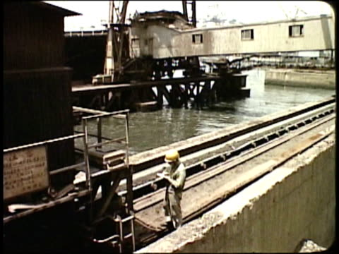 1963 montage iron ore on conveyor belt being transported to mill / japan - metal industry stock videos & royalty-free footage