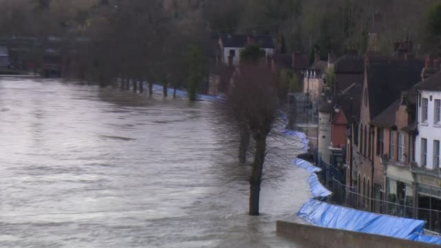 ironbridge and bewdley residents evacuated as flood defences breached; england: shropshire: ironbridge: ext high river and blue flood barrier zoom in... - blue stock videos & royalty-free footage