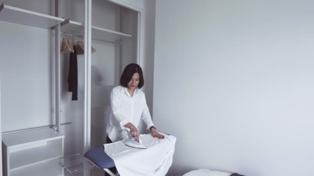 ironing at white room - ironing board stock videos & royalty-free footage