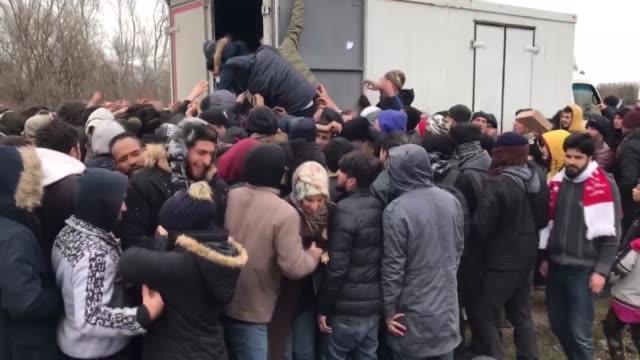 stockvideo's en b-roll-footage met irregular migrants waiting near turkey's border with greece at pazarkule border in karaagac neighbourhood of edirne stampede as they try to receive... - op hol slaan