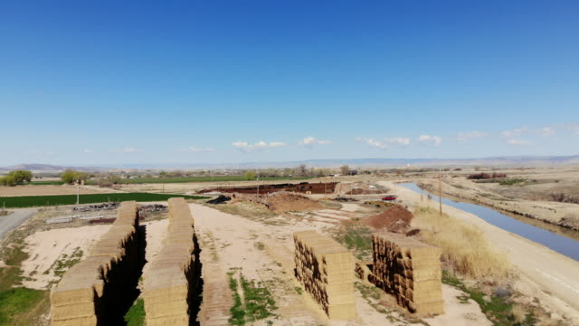 irrigation canal haystack and feedlot in western usa water sourced from the colorado river 4k aerial video - haystack stock videos & royalty-free footage