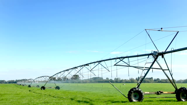 irrigation machine on meadow in blue sky